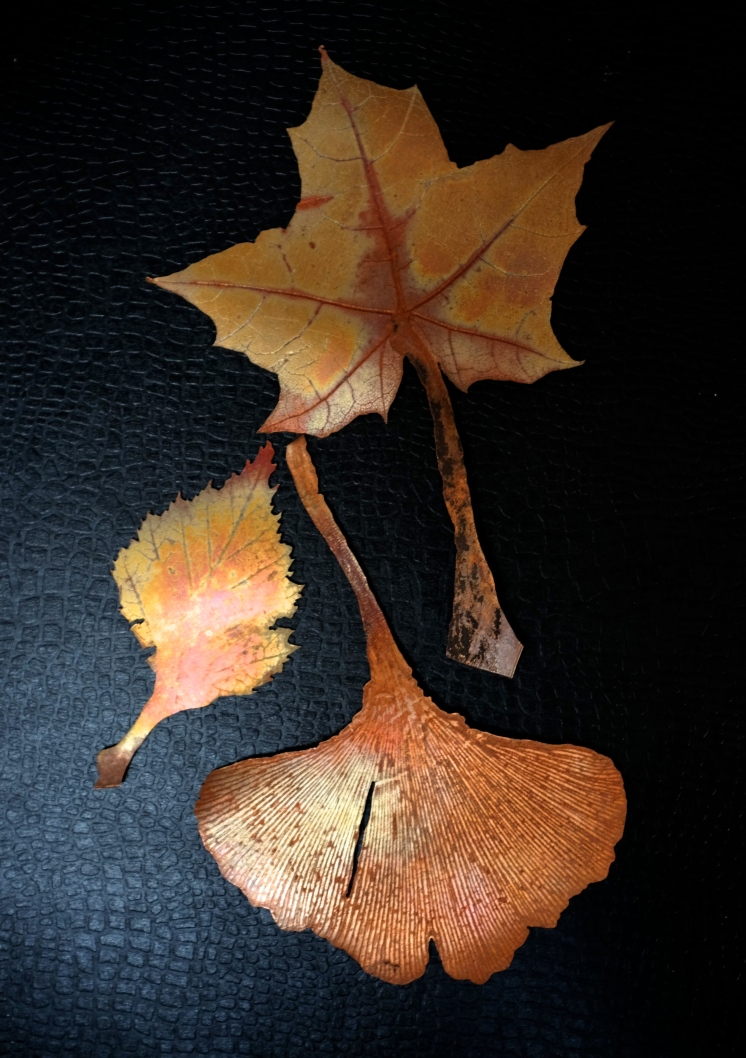 Fire-coloured copper leaves, rolled and pierced.