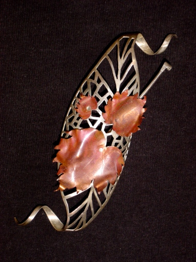 Sterling silver spirals and fire-coloured copper leaves. First piece of fretwork produced for a college project.